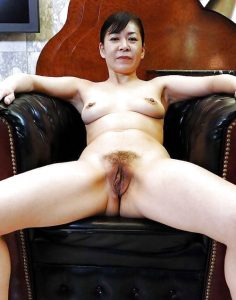 Older amateur Asian women sitting in a chair mature and proud