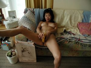 Mature Asian mom with a grin using a banana on her tight pussy