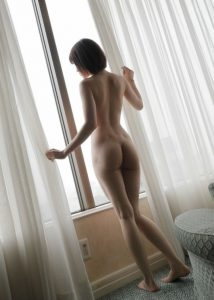 Sexy photo of an Asian Milf longingly looking out a window naked